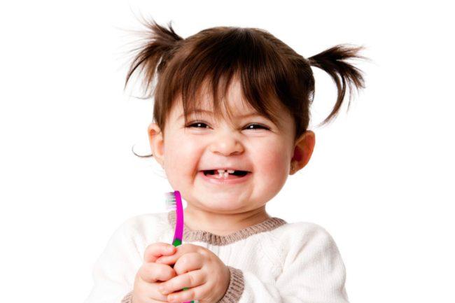 niña pequeña sonríe sujetando un cepillo de dientes